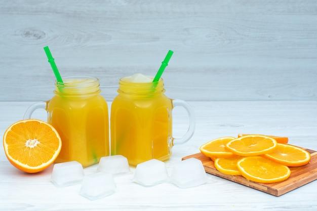 Orangensaftgetränk mit eiswürfeln auf holzoberfläche
