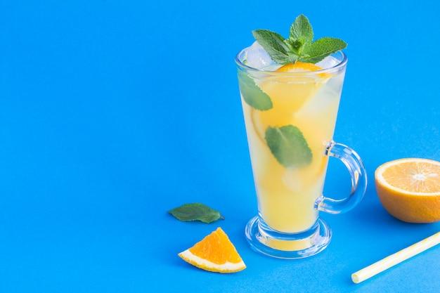 Orangensaftgetränk oder limonade mit minze und eis im glas auf blau. speicherplatz kopieren.