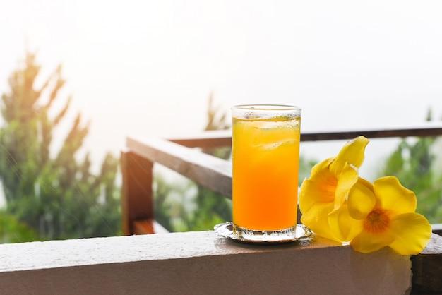 Orangensaftglas mit gelber blume auf balkon mit regentropfen am morgen