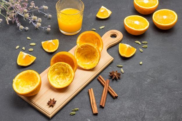 Orangenschale auf schneidebrett. zimtstangen und ein glas orangensaft auf dem tisch. schwarzer hintergrund. ansicht von oben