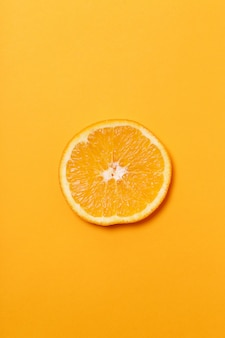 Orangenscheibe isoliert auf orange oberfläche