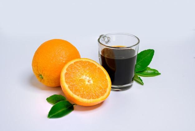 Orangenscheibe mit frischem orange und heißem kaffee und grünem blatt lokalisiert auf weißem hintergrund.