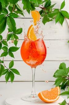 Orangenscheiben fallen in spritzenden aperol-cocktail.