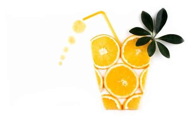 Orangenscheiben in form eines glases mit einem strohhalm und tropfen frischen orangensaftes, draufsicht, nahaufnahme.