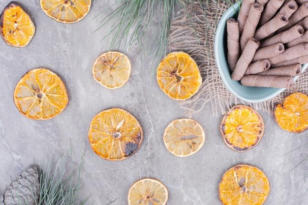 Orangenscheiben mit waffelstangen in einer blauen tasse