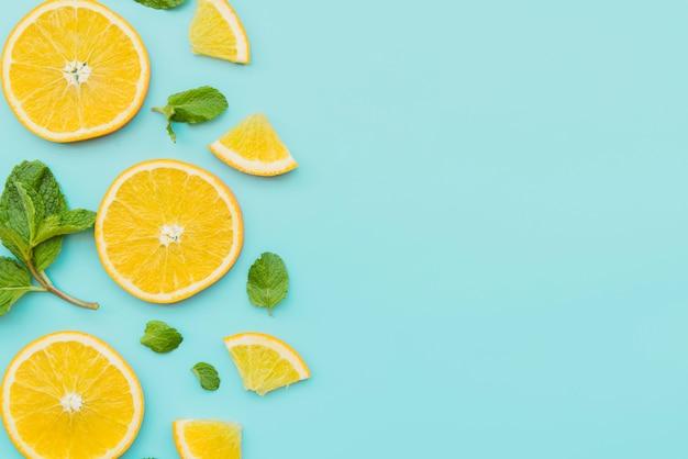 Orangenscheiben und tadellose blätter auf hintergrund