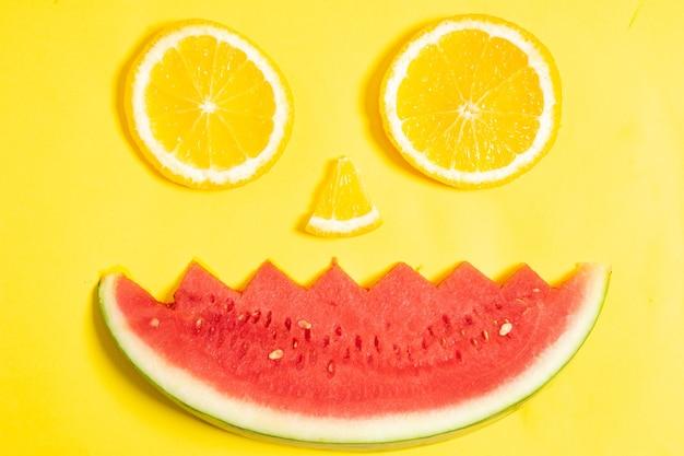 Orangenscheiben und wassermelonenstücke in form eines menschlichen gesichts angeordnet