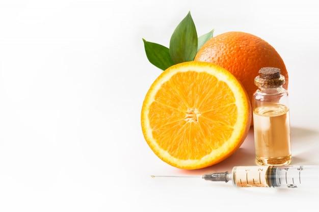 Orangenscheibenfrucht, plastikwegwerfspritze und flasche mit öl oder wesentlichem. isoliert auf weiss nahansicht.