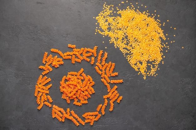 Orangenspiralen aus nudeln und linsen gegen eine dunkelheit