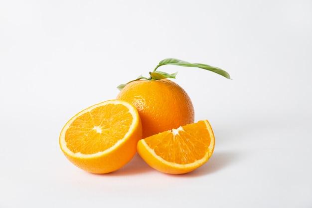 Orangenteile und ganze früchte mit grünen blättern schneiden