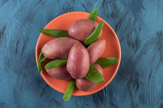 Orangenteller mit süßen bio-kartoffeln auf blauer oberfläche.