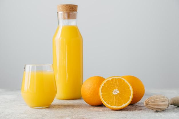 Orangenzitrusfruchtsaft in der glasflasche, in den frischen orangen und im quetscher
