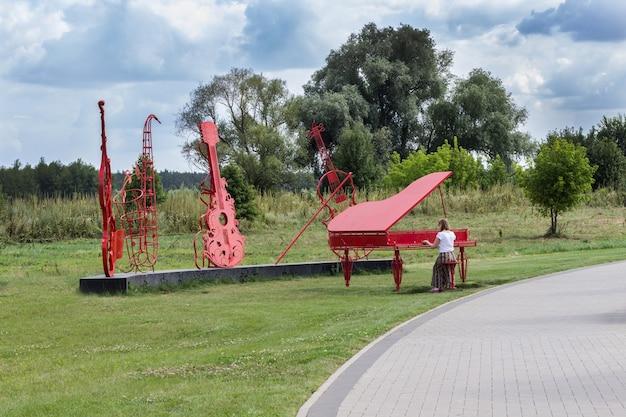Orchesterinstallation im park, rotes klavier, cello und geige. frau ahmt das klavierspielen nach. abstraktes bild im hintergrund der natur.