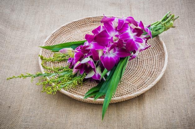 Orchideen-blumenstrauß im platzset auf sackleinen