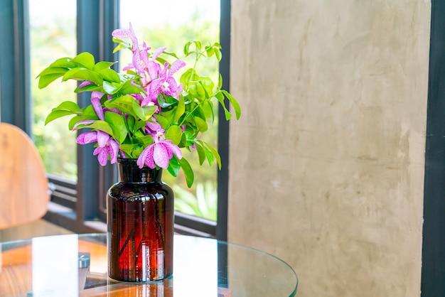 Orchideenblüten in vasendekoration auf dem tisch im café-café-restaurant