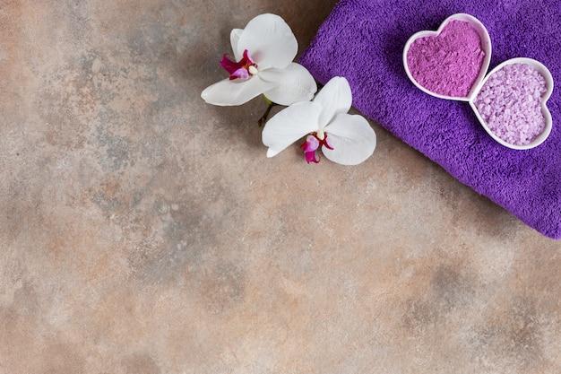 Orchideenblume, aroma-meersalz, natürlicher kosmetischer lehm und handtuch.
