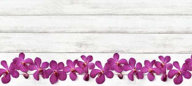 Orchideenblume auf weißem holzbrett mit kopienraum.