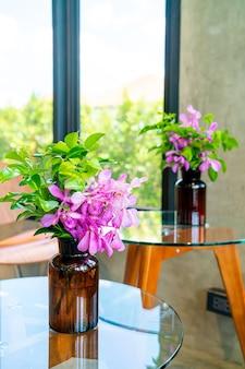 Orchideenblumen in der vasendekoration auf dem tisch im café-restaurant des coffeeshops