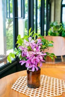 Orchideenblumen in der vasendekoration auf tisch