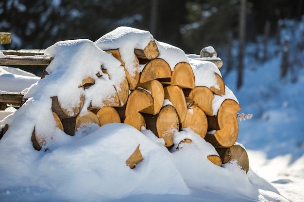 Ordentlich angehäufter stapel gehacktes trockenes stammholz draußen bedeckt mit schnee am sonnigen tag des hellen kalten winters, abstrakt