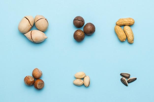 Ordentlich angeordnet zwei reihen verschiedener nüsse auf einem blau. vegetarisches essen. flach liegen.