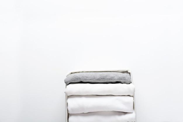 Ordentlich gefaltete weiße und graue kleidung in einem behälter für einen kleiderschrank oder eine reise auf weiß. bestellung im kleiderschrank.