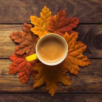 Ordentlich gesetztes herbstlaub um kaffeetasse