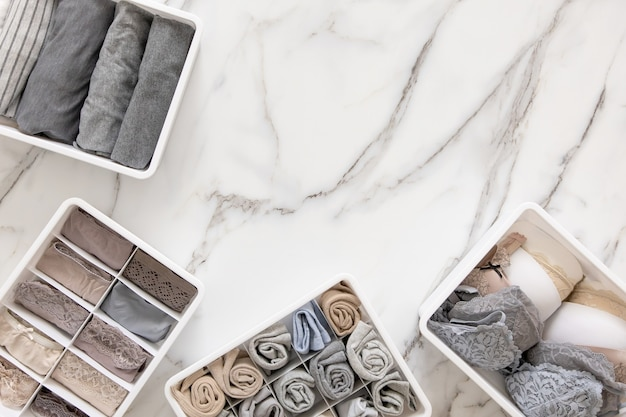 Ordentlich und ordentlich gefaltete dessous in organizer schubladenunterteiler auf weißem marmor
