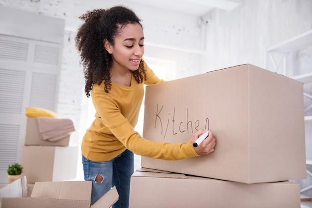 Ordentlich verpackt. hübsches mädchen mit den lockigen haaren, das eine schachtel mit küchenbesteck signiert und lächelt, während es sich darauf vorbereitet, aus der alten wohnung auszuziehen