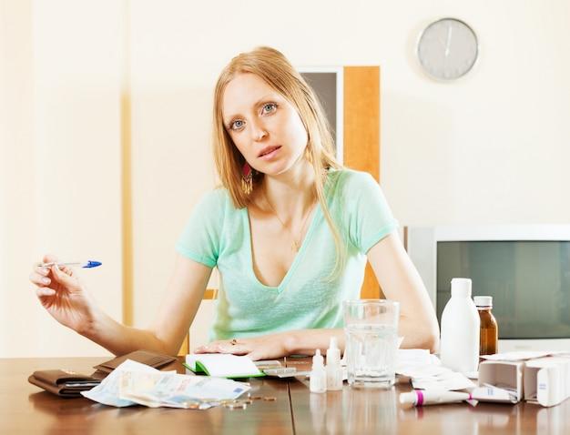 Ordentliche blonde frau mit medikamenten und geld