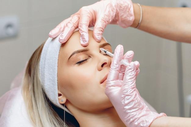 Ordentliche kosmetikerin, die botox in den stirnbereich injiziert, charmante patientin. anti-aging-behandlungskonzept
