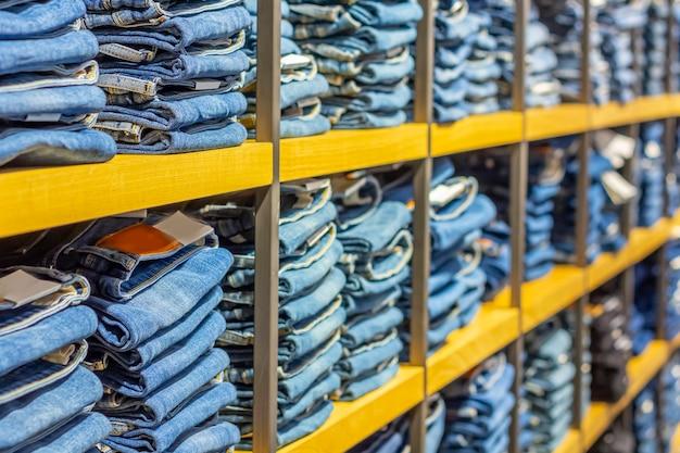 Ordentliche stapel gefalteter jeans in den ladenregalen