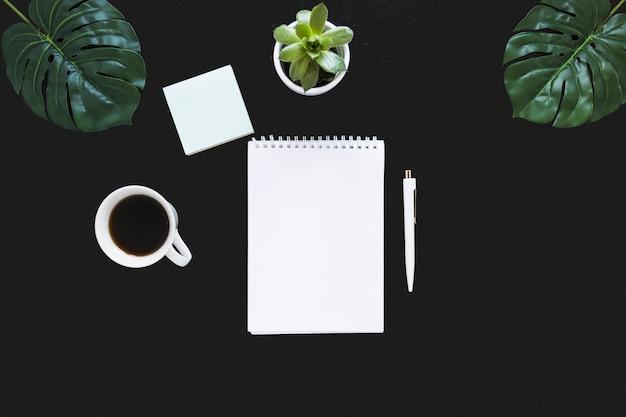 Ordentlicher arbeitsplatz mit notizbuch und kaffee