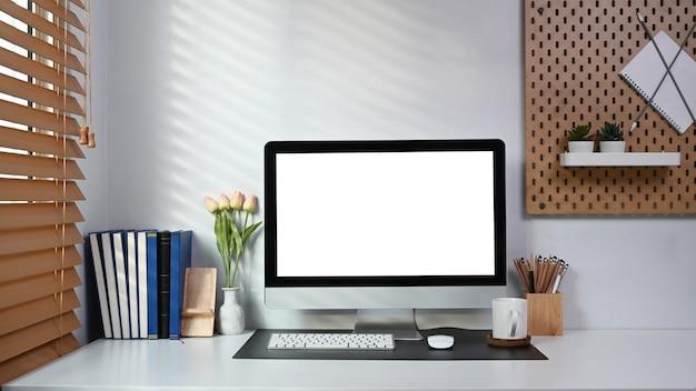 Ordentlicher und geordneter arbeitsplatz mit computer, büchern und bürobedarf auf weißem tisch.
