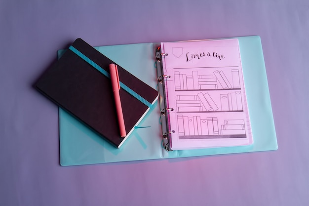 Ordner von oben mit schreibheft und stift. papier mit bücherregalzeichnung.
