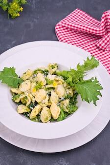 Orecchiette alla pugliese, hausgemachte italienische pasta. orecchiette mit rübenoberteilen. traditionelles essen aus süditalien auf weißem grund. speicherplatz kopieren