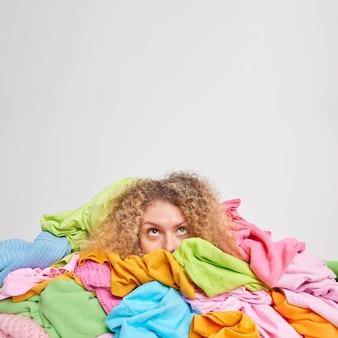 Organisationskonzept für kleidung. aufmerksame lockige behaarte frau, umgeben von mehrfarbiger wäsche, die sich oben konzentriert, sammelt kleidung in gutem zustand für den verkauf einzeln auf weißem wandkopierraum nach oben
