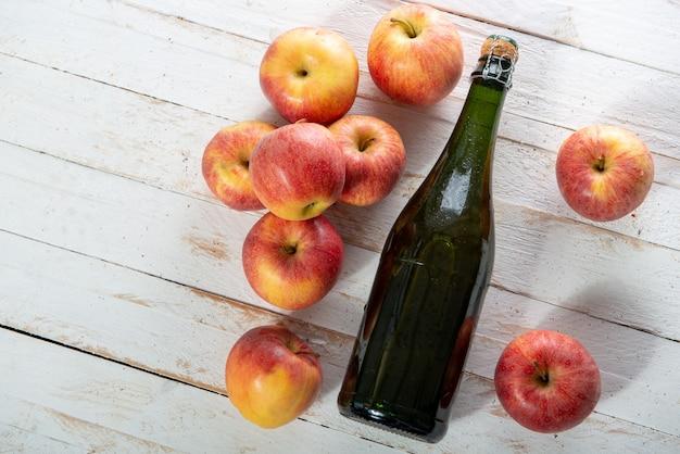 Organische äpfel mit einer flasche apfelwein auf weißem holztisch