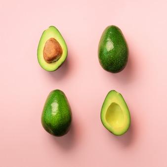 Organische avocado mit samen, avocadohälften und ganzen früchten auf rosa hintergrund. grünes avocados-muster im minimal flachen lay-stil.