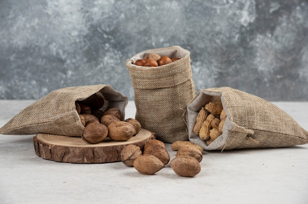 Organische geschälte haselnüsse, erdnüsse und walnüsse in sackleinen auf marmortisch.