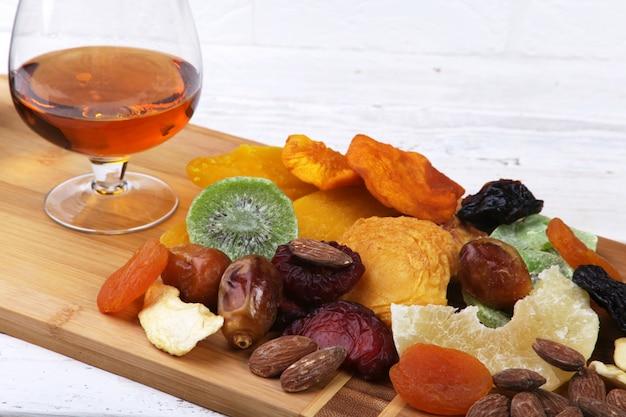 Organische gesunde sortierte trockenfrüchte und gläser mit kognak oder whisky auf weinbrett