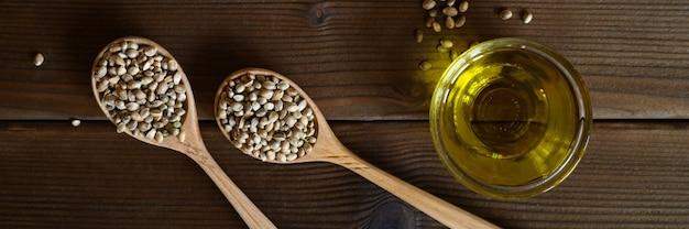 Organische getrocknete hanfnahrungsmittelsamen in einer zusammensetzung mit küchenobjekten auf einem holztisch. flach liegen.
