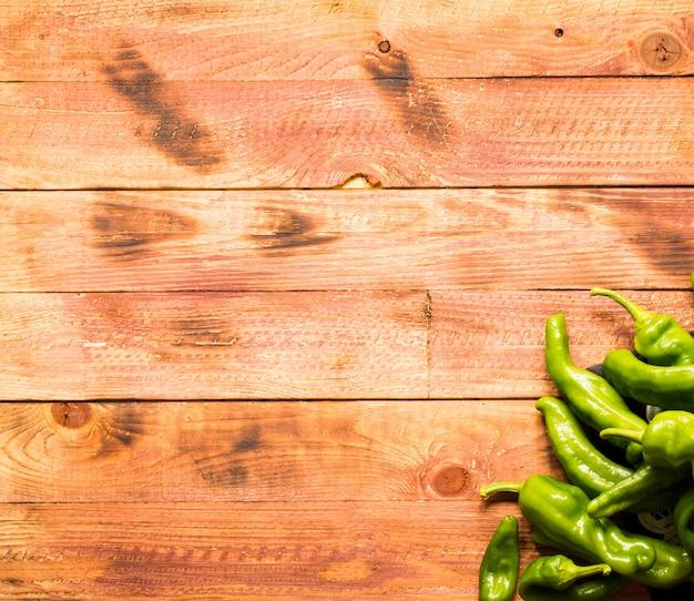 Organische lange grüne paprikas, auf hölzernem hintergrund. ansicht von oben