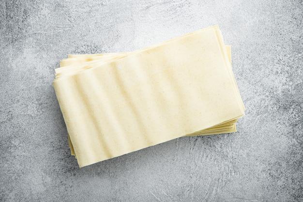 Organische lasagne-nudelblätter gesetzt, auf grauem steintisch, draufsicht