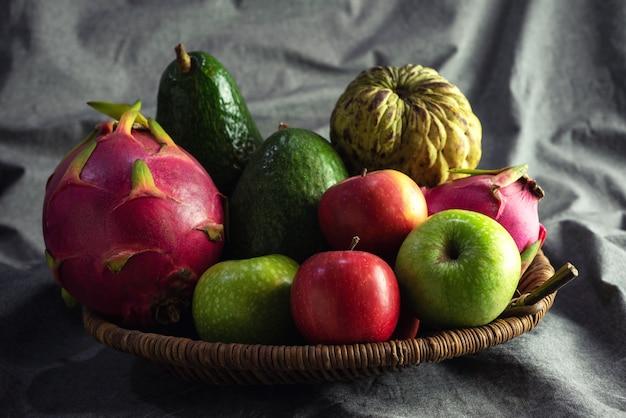 Organische mischung trägt apfel, avocado, vanillepudding apple, pitahaya im korb früchte