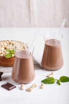 Organische nicht molkerei-acajounuss-schokoladenmilch in der glas- und holzplatte mit acajounüssen auf einem grauen beton.