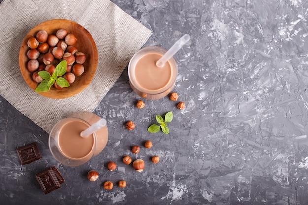 Organische nicht molkereihaselnuss-schokoladenmilch in der glas- und holzplatte mit haselnüssen auf einem grauen beton.