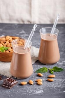 Organische nichtmilchmandel-schokoladenmilch in der glas- und holzplatte mit mandelnüssen auf einem schwarzen konkreten hintergrund