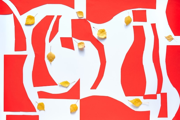 Organische orange, rote papierformen mit herbstgelben blättern auf weiß