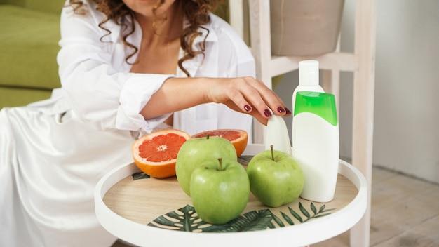 Organische orange und grüne äpfel auf dem natürlichen holztisch. selektiver fokus. biolebensmittel-, kosmetik- und spa-konzept